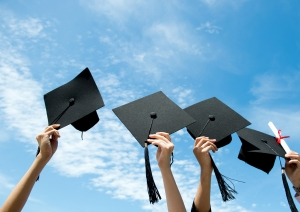 Many hand holding graduation hats on background of blue sky.