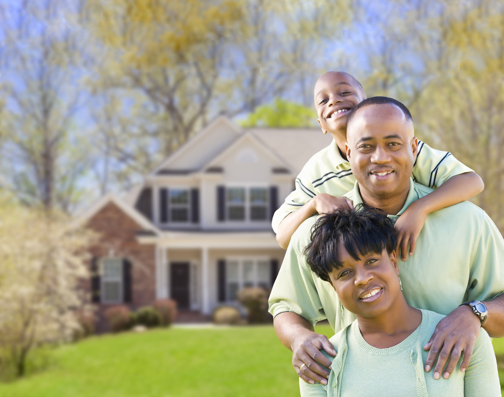 Happy African American Family In Front of Beautiful House.