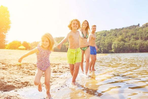 Familie mit Kindern beim Baden am See im Sommer